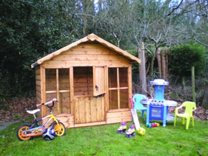 Wooden playhouse and toys on lawn