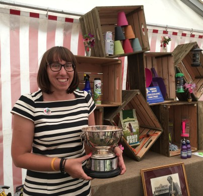 Beth Bright holding winning trade stand trophy