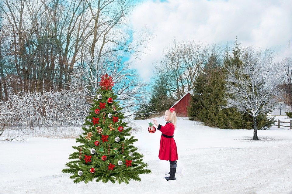 Decorated Christmas tree in snow with girl in red