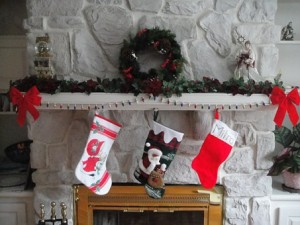 Three Christmas stockings hanging over mantlepiece