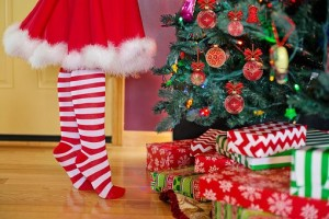 Woman in red stripe stockings decorating Christmas tree