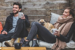 Couple with dog cosy and drinking coffee