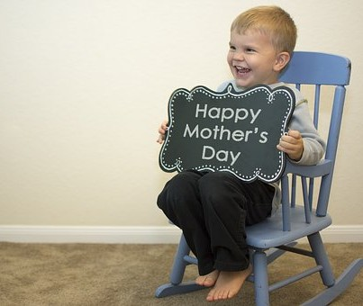 Child with chalk board sign Happy Mother's Day