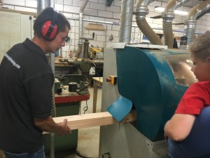 man working wood machine watched by boy