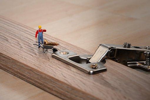 Tiny workman with screw and wheelbarrow