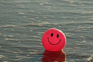 Red ball with smiley painted face in sea