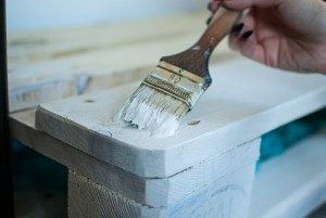 Person painting wood ice blue with brush
