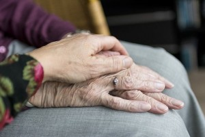 Care giver holding older person\s hand