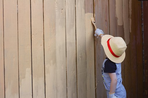 child in hat painting fence