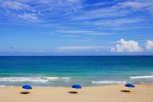 three parasols on sandy beach